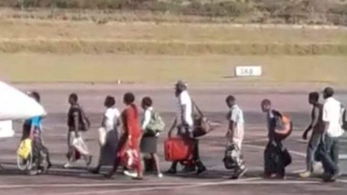 Haitians walking to the plane.